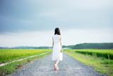 Fototapety 田舎道を歩く女性