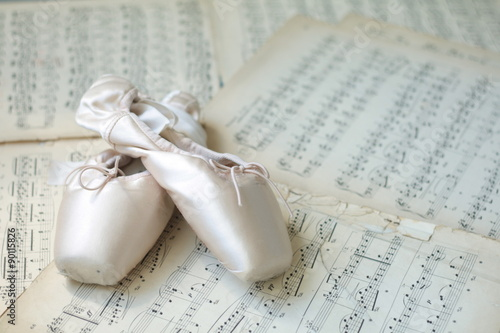 Poster Ballet shoes laying on the old piano musical notes