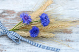 Cereal ears with cornflowers lying on wood