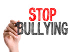 Hand with marker writing the word Stop Bullying poster