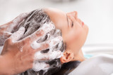 Fototapety Cheerful young woman has her hair washed in beauty shop