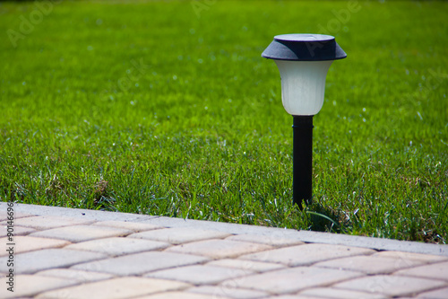 Poster Solar Lantern is on the green lawn next to a paved garden path
