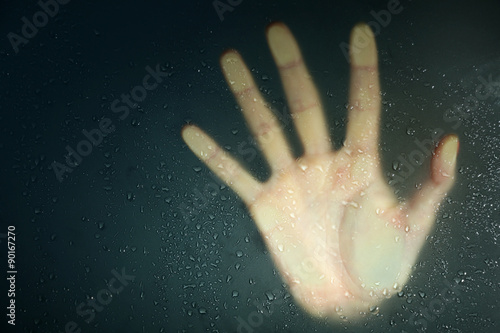 Foto op Canvas UFO Female hand behind wet glass, close-up