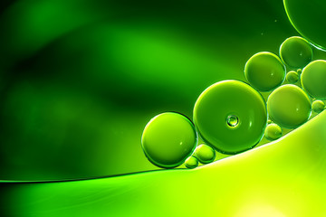 Abstract background, green oil droplets on water surface.