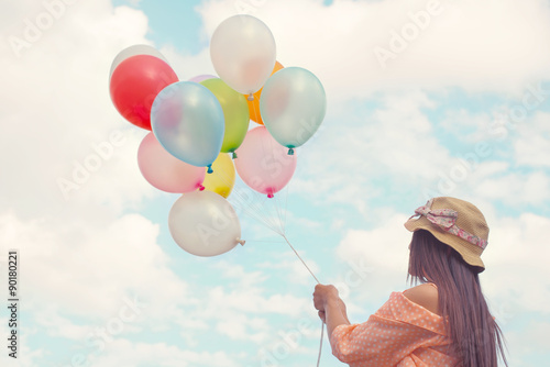 Poster Vintage pastel color of Happy young red hair woman holding colorful balloons and flying on clouds sky background