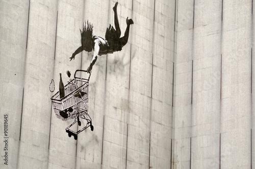 Banksy falling shopper graffiti, London - 90189645
