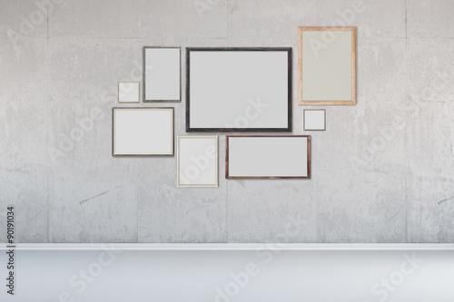 Viele Bilderrahmen an Wand aus Beton