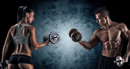 Athletic man and woman with a dumbells. © bondarchik