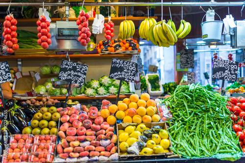 In de dag Barcelona Price tags on market stall, fruits and vegetables for sale at La Boqueria. La Boqueria is a large public market in the Ciutat Vella district of Barcelona, Catalonia, Spain
