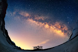 Teamwork and support. A group of people are standing together holding hands against the Milky Way in the mountains.  - 90230833