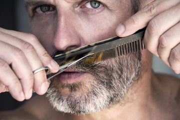 man trimming his beard