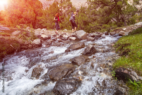 Poster Two hikers crossing fast flowing river People going across mountain creek with f
