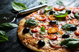 Pizza with salami, olives and basil