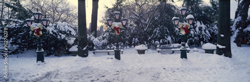 Panoramic view of Christmas wreath on lampposts in Central Park, Manhattan, New York City following winter snowstorm - 90276278