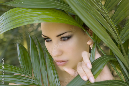 Sexy beautiful woman hiding behind the palm leaves. Beautiful st - 90299622
