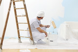 painter man at work takes the color with paint roller from bucket