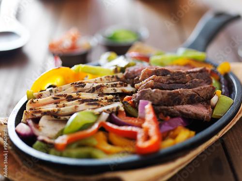 Plagát, Obraz steak and chicken fajitas close up in cast iron fajita skillet