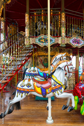 Staande foto Imagination Old French carousel in a holiday park. Three horses and airplane on a traditional fairground vintage carousel. Merry-go-round with horses.