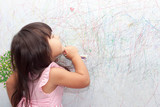 Fototapety girl drawing with crayons on the wallpaper