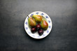Fresh pears and plums on ornamental plate and grey kitchen table