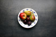 Fresh fruits plate on grey kitchen table