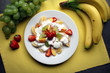 Fresh fruit salad with yoghurt on kitchen table - healthy eating background