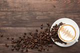 Fototapety Coffee cup and coffee beans on wooden background. Top view.