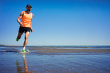 A man in a sports uniform is running along the shore of the lake - Fine Art prints