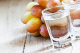 Grappa in a small glass and ripe grapes on old wooden table, sel