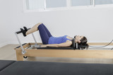 Woman, pilates with reformer bed.