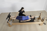 woman and instructor in reformer bed, pilates.