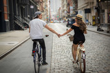 Lovers riding bicycle together holding hands - 90662661