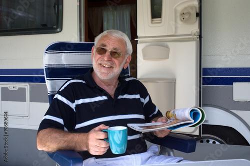 Lachender Rentner sitzt vor seinem Wohnwagen beim Campingurlaub Poster