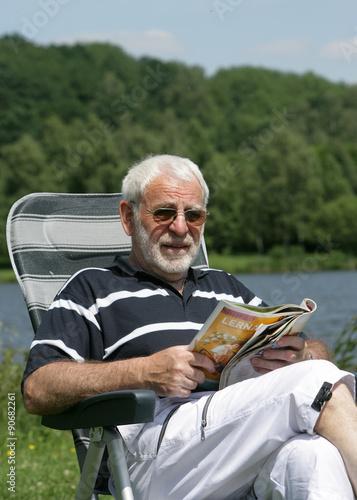 Senior beim Campingurlaub an einem See sitzend Poster