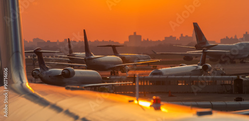 Fototapeta Sunset at the airport with airplanes ready to take off