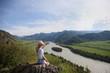 Постер, плакат: девушка сидит на камне с видом на горы и реку