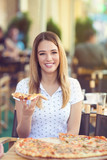 Cheerful young woman eating pizza in the outdoor cafe