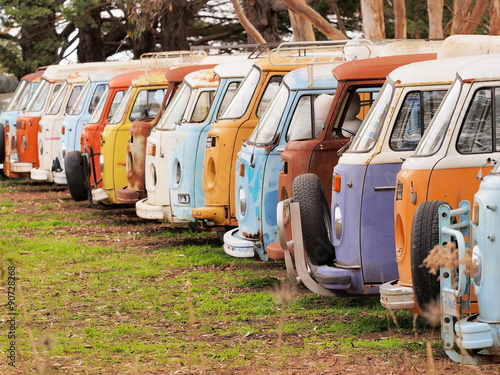 Plagát, Obraz Row of defunct colorful and run down desolate vans of all the same Volkswagen Bu