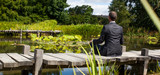 Fototapety corporate green break - meditating middle age male professional sitting on a wooden bridge in the middle of an asian-like green pond for company wellbeing,back view with park foreground
