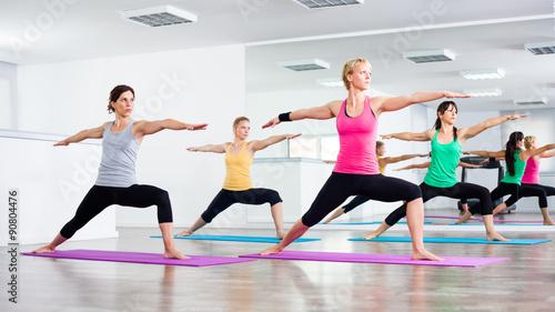 Four girls practicing yoga, Virabhadrasana / Warrior pose