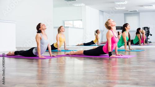 Obraz na płótnie Cztery dziewczyny ćwiczenia jogi, Bhujangasana / Cobra Pose
