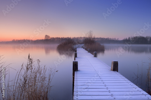 Fototapeta Boardwalk on a lake at dawn in winter, The Netherlands