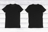 Fototapety Two black blank T-shirts on a white wooden background