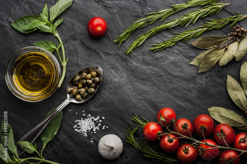 Herbs mix with tomatoes and olive oil on the black stone table