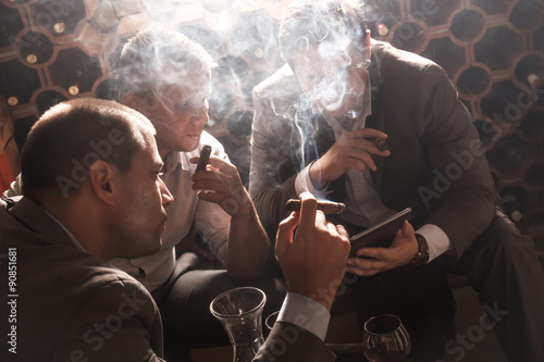 Poster Three businessmen sitting in the wine cellar drinking wine and smoke cigar, resting after a hard day at work