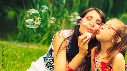 Mother and child blowing soap bubbles outdoor.