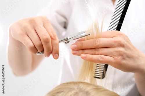 Podcinanie rozdwojonych końcówek włosów.Fryzjer strzyże kobietę w salonie fryzjerskim