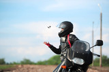 Fototapety The charming girl in a black helmet sits on the motorcycle and t