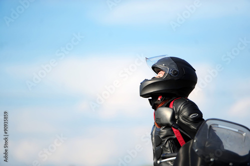 fototapeta na ścianę The girl motorcyclist sits on the motorcycle in a helmet