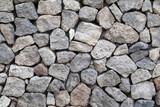Texture of gray rough granite stone wall